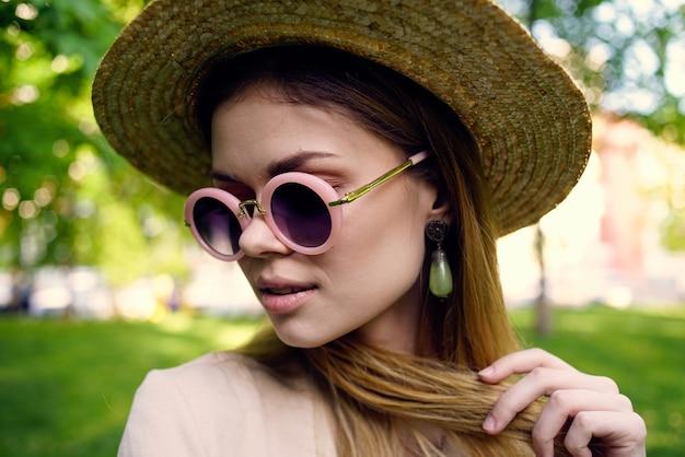 Жизнерадостная женщина в солнцезащитных очках и шляпе на открытом воздухе в парке гуляет по зеленой траве. фото высокого качества