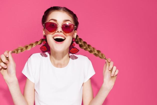 ピグテールピンクの背景のファッショナブルな服の夏を保持しているサングラスの陽気な女性