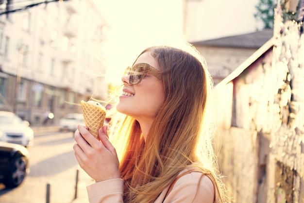 거리에 도시의 선글라스에 쾌활한 여자는 아이스크림과 함께 산책