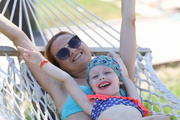 Жизнерадостная женщина в солнечных очках лежит на гамаке под солнцем с дочерью.