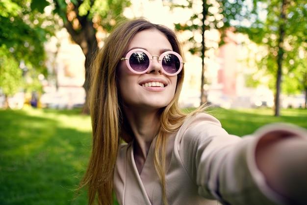 Жизнерадостная женщина в солнечных очках на открытом воздухе в парке зеленая трава свежего воздуха. фото высокого качества