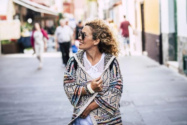 휴일에 거리에 걷는 선글라스에 쾌활 한 여자. 겨울 동안 재킷을 입고 거리를 걷는 젊은 여성. 도시 거리를 걷는 동안 웃는 젊은 여자.