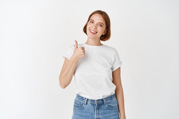 티셔츠를 입은 쾌활한 여성이 엄지손가락을 치켜들고 웃고, 승인하고 좋아합니다. 짧은 머리와 자연스러운 외모를 가진 소녀는 흰 벽에 서서 좋은 일을 칭찬합니다