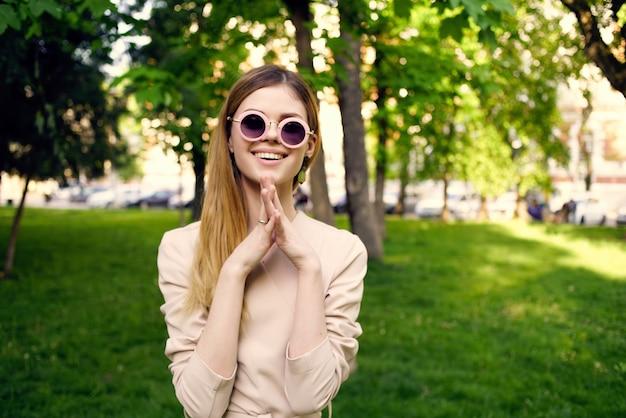 公園の緑の芝生の夏の散歩で陽気な女性