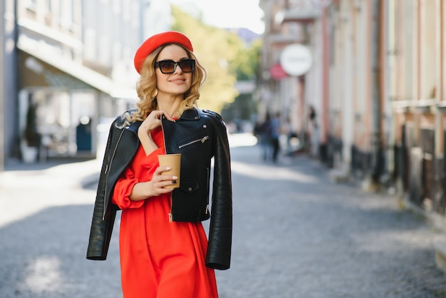 Веселая женщина на улице пьет утренний кофе в солнечном свете