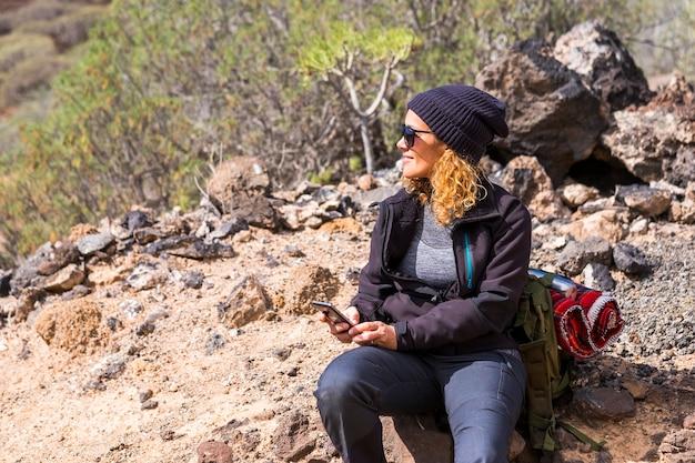 Веселая женщина в походе с рюкзаком и сценой пустынных гор вокруг