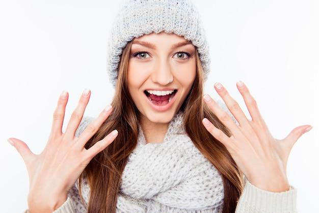 Веселая женщина в теплой шапке и шарфе, жестикулирующая руками