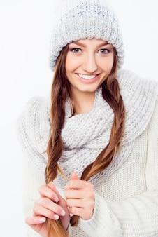 彼女の髪を保持している暖かい帽子とスカーフの陽気な女性