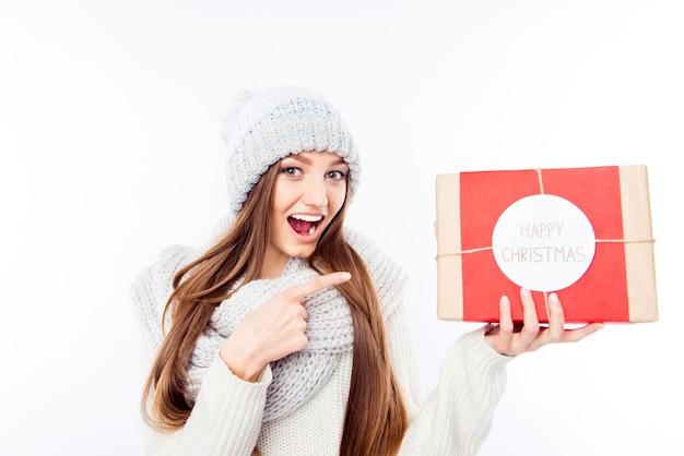 Веселая женщина в теплой шапке и шарфе держит пакет и поздравляет с рождеством