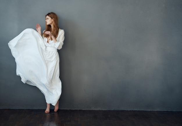 白いドレスの陽気な女性ダンスエンターテインメントエレガントなスタイルの暗い背景