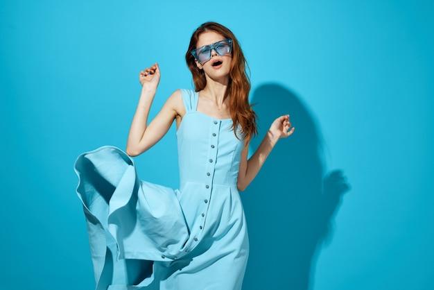 파란 안경 스튜디오 격리 된 배경 포즈 흰 드레스에 쾌활 한 여자. 고품질 사진