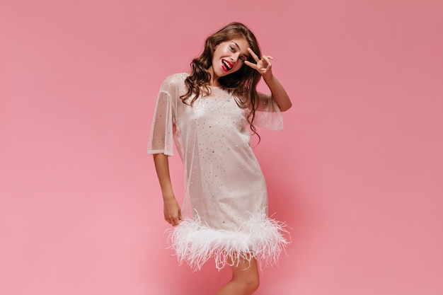 Веселая женщина в белом платье широко улыбается на розовой стене