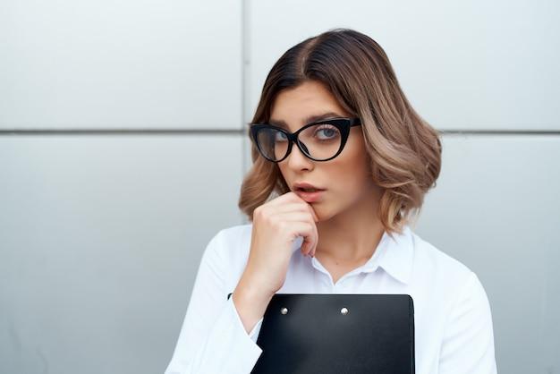 白いシャツを着た陽気な女性は、オフィスの公式実業家を文書化します