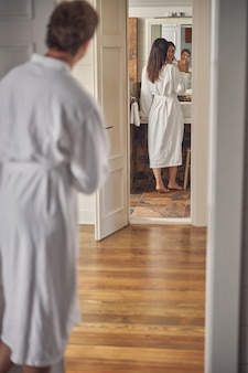 그녀의 이빨을 닦는 동안 흰색 부드러운 목욕 가운에 쾌활 한 여자