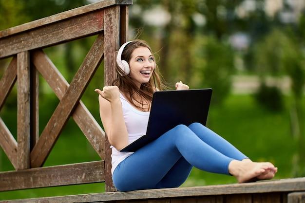 Веселая женщина в беспроводных наушниках делает удаленную работу с ноутбуком на открытом воздухе
