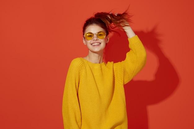 彼女の頭のファッションの赤い背景を保持している黄色いメガネの陽気な女性
