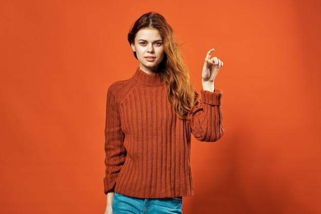黄色のセーターファッション髪型笑顔カジュアルウェアスタジオ赤い背景の陽気な女性