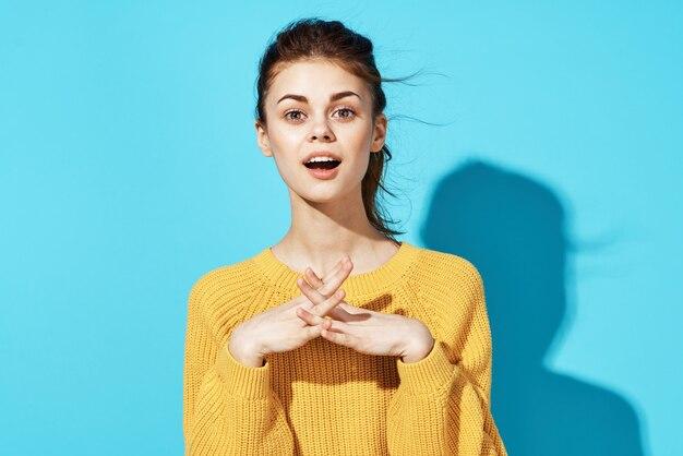 ファッションポジティブなポーズをとる黄色のセータースタジオで陽気な女性