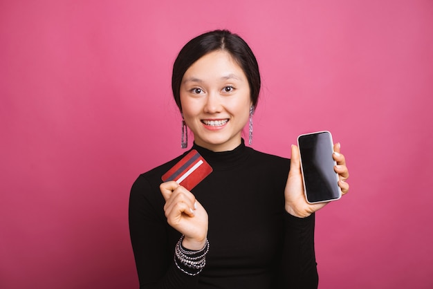 Cheerful woman is holding a red card a phone on pink background.