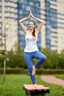 Веселая женщина занимается йогой на скамейке в парке