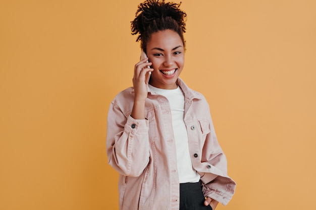 Cheerful woman in jacket talking on smartphone