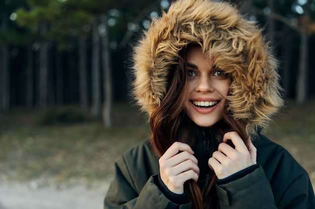 Cheerful woman in a jacket with a hood nature lifestyle look ahead.