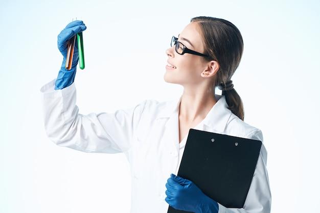 陽気な女性実験助手化学溶液は、研究の光の背景を分析します
