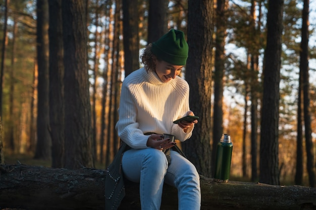 Веселая женщина смеется, читая текстовое сообщение или прокручивая социальные сети, гуляя в осеннем лесу на выходных