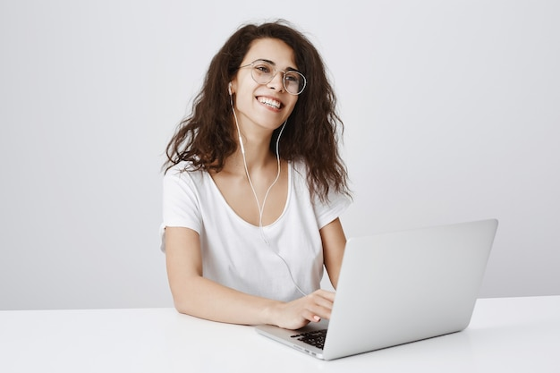 ノートパソコンでの作業と音楽のイヤホンを聞いている間笑っている陽気な女性