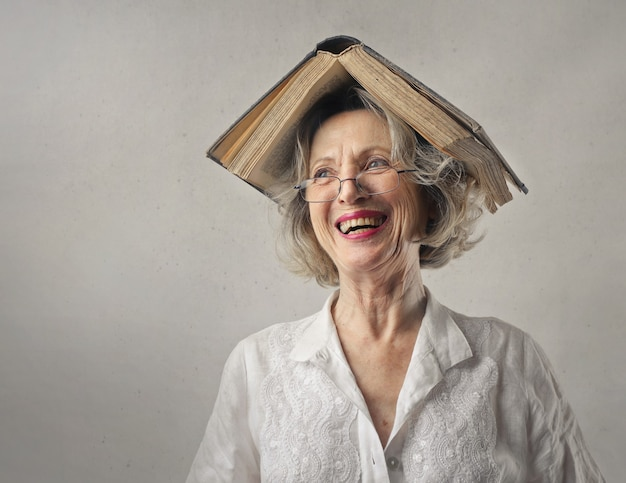 Cheerful woman, laughing with a book on her head
