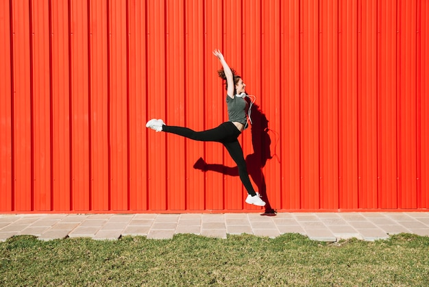 Cheerful woman leaping near red wall