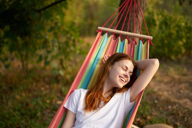 Cheerful woman lies in a hammock in nature sun rest