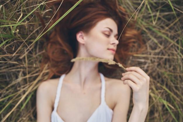 陽気な女性が野外夏休みに藁の上に横たわる