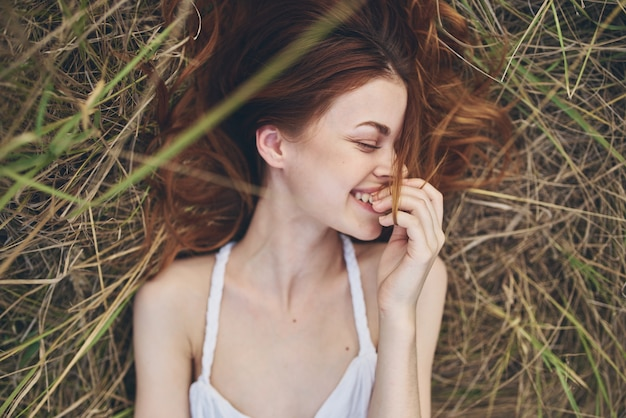 Cheerful woman lies on a straw in a field nature closeup