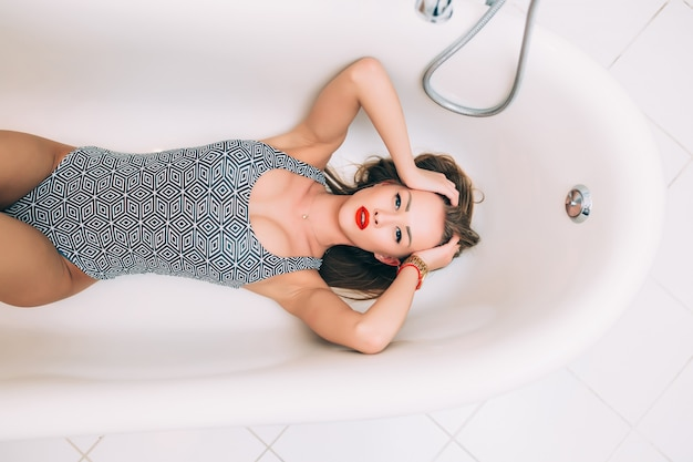 A cheerful woman lies in a white foam bathtub resting clean skin