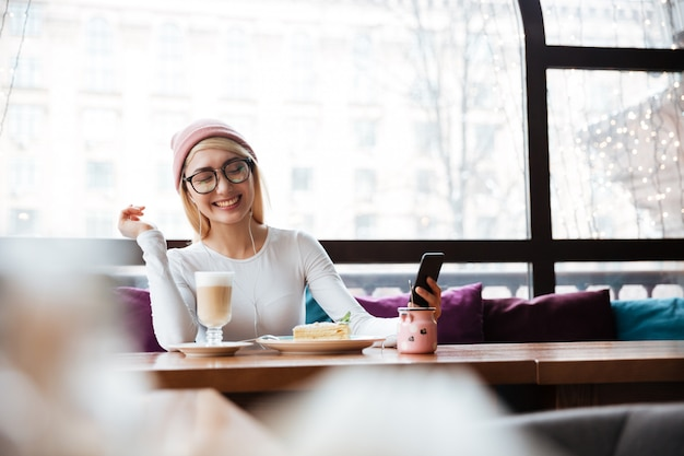 Cheerful woman listening to music from cell phone in cafe