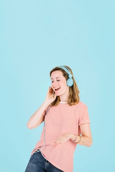 Cheerful woman listening to music in headphones