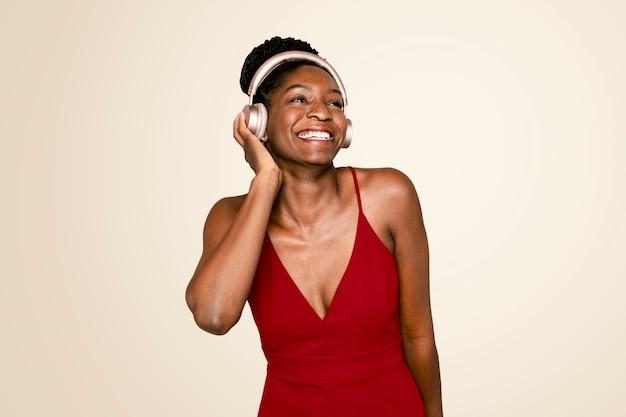 Cheerful woman listening to music through headphones digital device