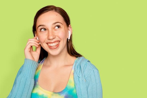 Веселая женщина, слушающая музыку через наушники