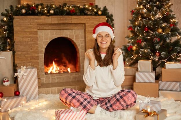 陽気な女性は幸せそうに見え、勝者のように拳を握りしめ、暖炉とクリスマスツリーの近くで屋内でポーズをとり、白いシャツ、市松模様のズボン、サンタの帽子をかぶって新年を祝います。