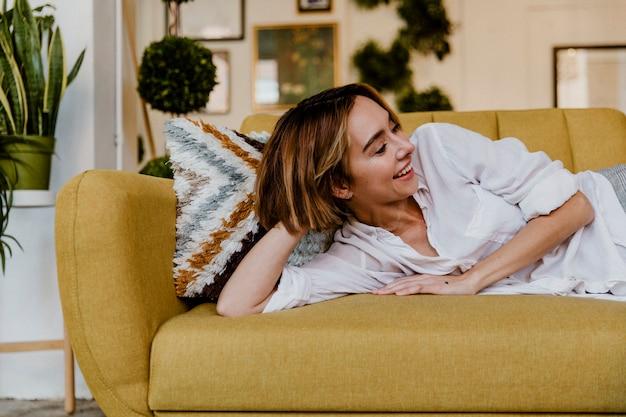 Веселая женщина, лежащая на горчично-желтом диване