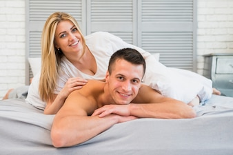Cheerful woman lying on young smiling man in bed