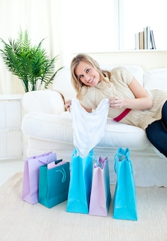 Cheerful woman lying on a white couch with shopping bags on the ground