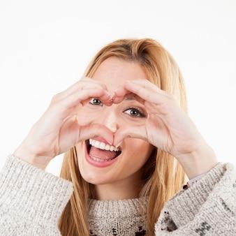 Cheerful woman making heart gesture