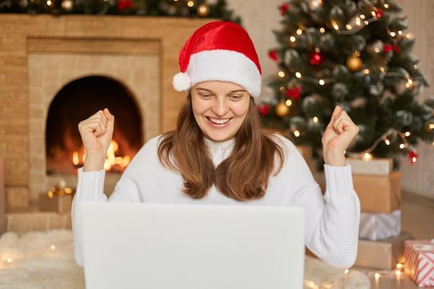 クリスマスの日にビデオ通話をして誰かに挨拶する陽気な女性は、幸せそうに見え、勝者のように拳を握りしめ、暖炉とクリスマスツリーの近くで屋内でポーズをとってデバイスの画面を見ます。