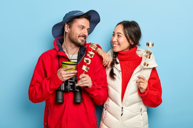 Cheerful woman and man have camping trip together, hold tasty marshmallow made on bonfire, look with smile at each other, spend leisure time in wild nature carry binoculars