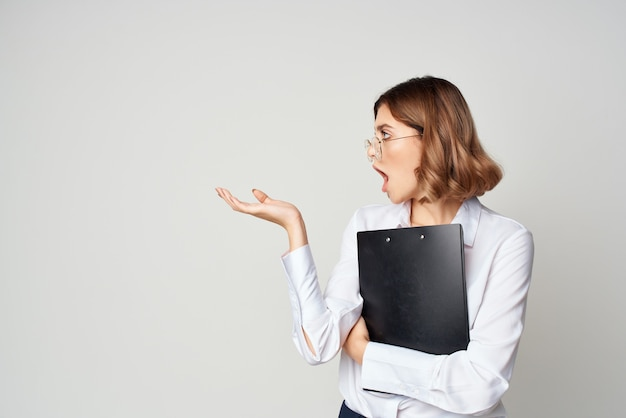 白いシャツのドキュメントの陽気な女性マネージャーはプロの仕事をします