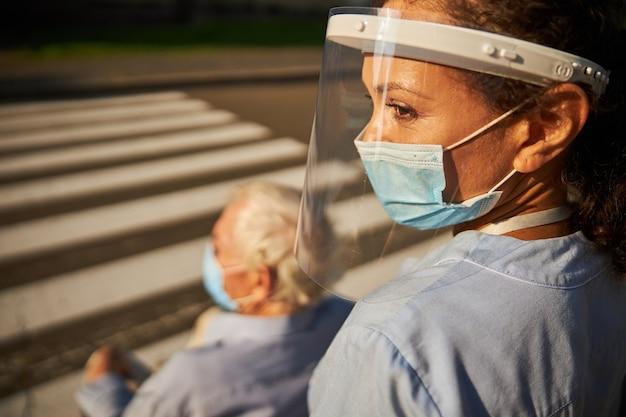 야외에서 성숙한 장애인 남자와 함께 걷는 파란색 제복을 입은 쾌활한 여성 의료 종사자