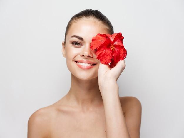 陽気な女性の裸の肩赤い花明るい背景
