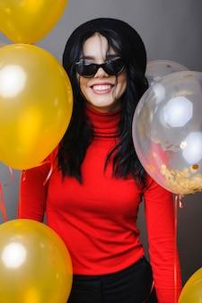 笑顔の風船の近くの陽気な女性